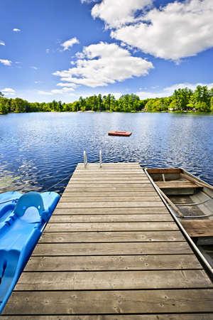 시골집: 캐나다 온타리오에있는 아름다운 여름 호수에 나무 독 스톡 사진