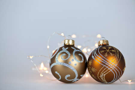 Two gold Christmas decorations and decorative lights on gray background with copy space photo