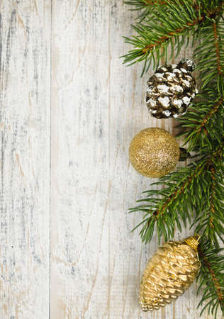 Christmas golden balls and pine cone on spruce branch with wooden background