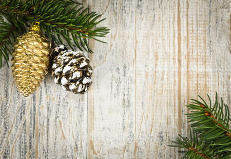 Christmas golden balls and pine cone on spruce branch with wooden background photo