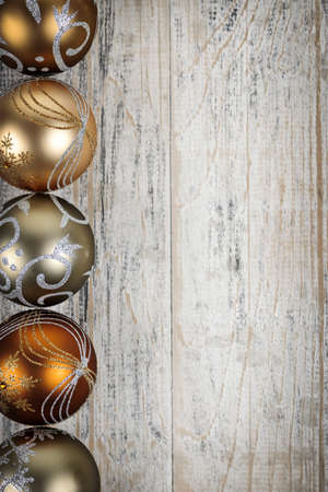 Row of golden Christmas balls with festive designs on wooden background Stock Photo - 16419296