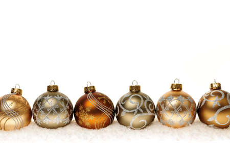 Row of golden Christmas balls with festive designs on snow photo