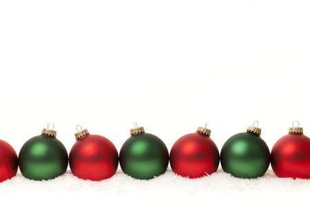Rij van groene en rode Kerst ornamenten op witte achtergrond