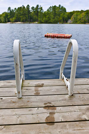 Wet footprints on dock with ladder and diving platform at lake in Onta Canada Stock Photo - 16419208