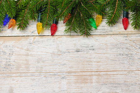 Multicolored Christmas lights on spruce branch with wooden background Stock Photo - 16556915