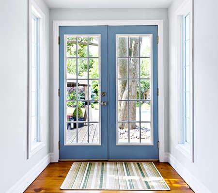 현관: 창은 햇볕이 잘 드는 뒷마당에 빠져 더블 안뜰 프랑스어 문 스톡 사진