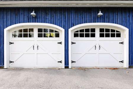青い家に窓を有する 2 つの白いガレージのドア 写真素材