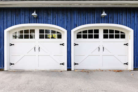driveways: Two white garage doors with windows on blue house Stock Photo