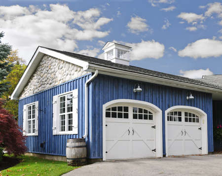 custom home: Double car garage with white doors and blue exterior Stock Photo