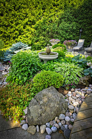 Lush perennial garden with fountain plants and trees photo