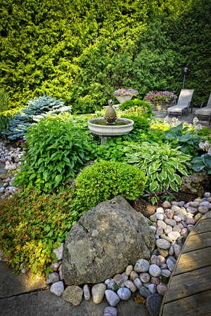 Lush Staudengarten mit Brunnen Pflanzen und Bäume Standard-Bild