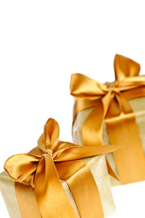 Two gift boxes in gold wrapping paper with ribbons and bows photo