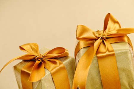 Two gift boxes wrapped in gold ribbons with copy space photo