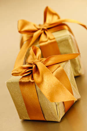 Two gift boxes in gold wrapping paper with ribbon and bow photo