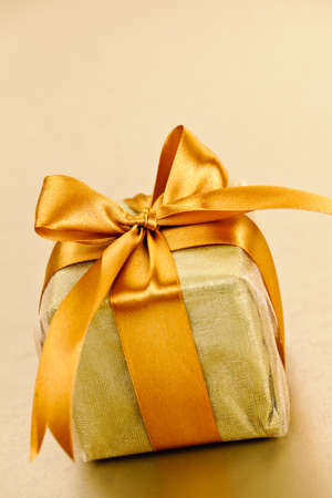 Gift box in gold wrapping paper with ribbon and bow Stock Photo - 16556722