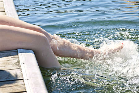 Girl sitting on dock splashing bare legs in lake photo