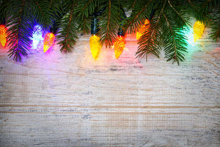 Multicolored Christmas lights on spruce branch with wooden background