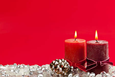 Christmas candles and decorations on red background photo