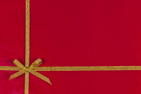 Red background of present wrapped with gold ribbon and bow photo