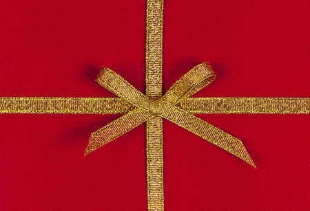 Red present wrapped with gold ribbon and bow Stock Photo - 16654693