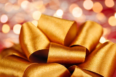Golden ribbon gift bow closeup with festive lights Stock Photo - 16654685