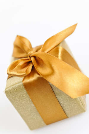 wrapped present: Gift box in gold wrapping paper with ribbon and bow Stock Photo
