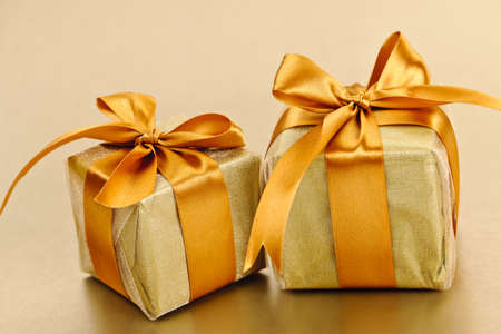 Two gift boxes in gold wrapping paper with ribbon and bow Stock Photo - 16654692