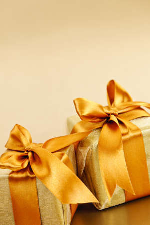 Two gift boxes wrapped in gold ribbons with copy space Stock Photo - 16654689