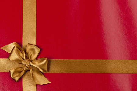 Red background of present wrapped with gold satin ribbon and bow Stock Photo - 16654696