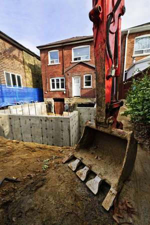 Backhoe scoop at residential home renovation construction site photo