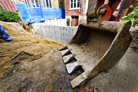 brick earth: Backhoe scoop at residential home renovation construction site
