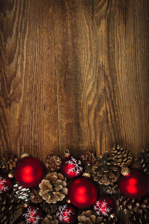 Rustic wood background with Christmas ornaments and pine cones photo
