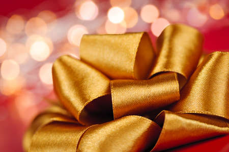 Golden ribbon gift bow closeup with festive lights Stock Photo - 16784820