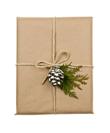 Christmas gift in brown wrapping and string with pine cone decoration isolated on white photo