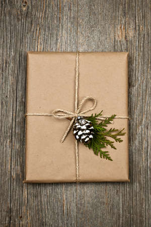 Christmas gift in brown wrapping and string with pine cone decoration on old wood background Stock Photo - 16784858