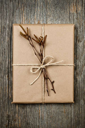 Simple gift package in brown paper decorated with birth branches on rustic wood background Stock Photo - 16784857