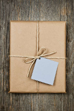 Gift package and card in brown paper wrapper tied with string on rustic wood background Stock Photo - 16784854