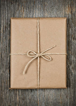 Gift package in brown paper wrapper tied with string on rustic wood background Stock Photo