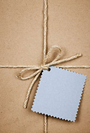 Gift package and blue tag in brown paper wrapper tied with string close up Stock Photo - 17570766