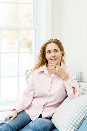 Smiling caucasian woman relaxing on couch by window Stock Photo - 17500451