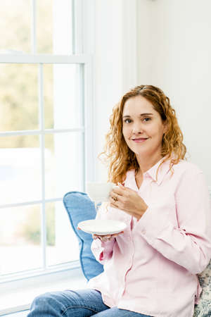 Smiling caucasian woman relaxing on couch by window holding cup of coffee Stock Photo - 17500447