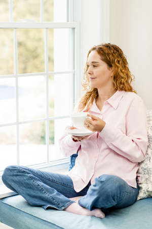 Smiling caucasian woman relaxing on couch by window holding cup of coffee Stock Photo - 17500453