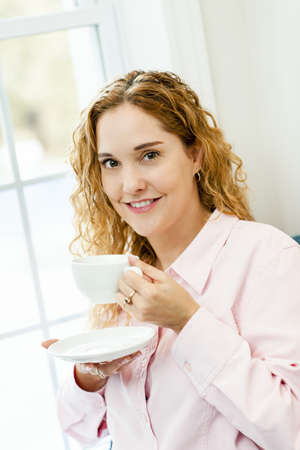 Smiling caucasian woman relaxing by window holding cup of coffee Stock Photo - 17500452