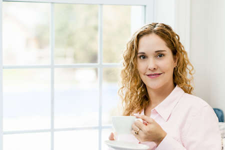 Smiling caucasian woman relaxing by window holding cup of coffee Stock Photo - 17500463