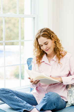 Smiling caucasian woman reading book by window at home photo