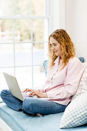 Caucasian woman using laptop computer sitting on couch at home Stock Photo - 17500454