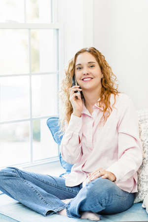 Smiling caucasian woman talking on cordless telephone at home photo