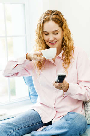 Smiling woman using cordless phone and drinking coffee photo