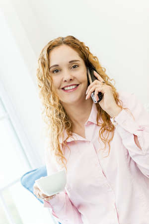 Smiling woman using cordless phone and drinking coffee Stock Photo - 17500448