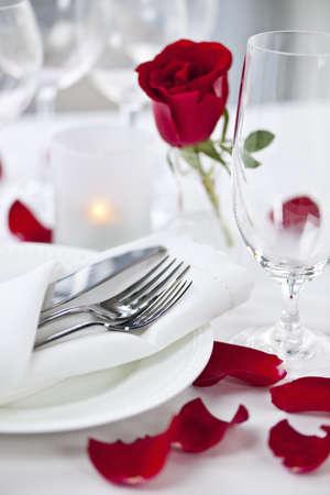 luz de velas: Ajuste de la tabla romántica con pétalos de rosa platos y cubiertos